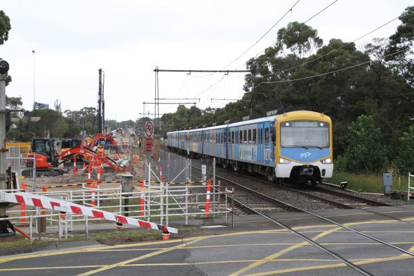 Citybound Siemens train passes level crossing removal works at Corrigan Road, Noble Park