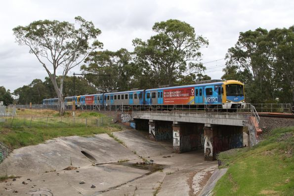 Siemens 714M leads a down Pakenham service crossing the Mile Creek bridge at Noble Park