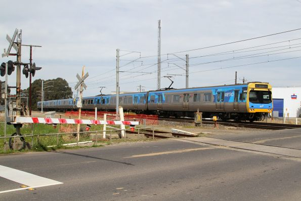 Comeng 366M leads an up Pakenham service over the Progress Street level crossing at Dandenong South