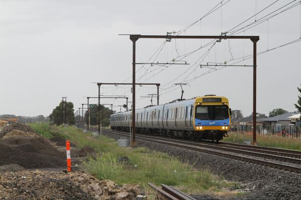 EDI Comeng train passes new housing between Officer and Beaconsfield stations