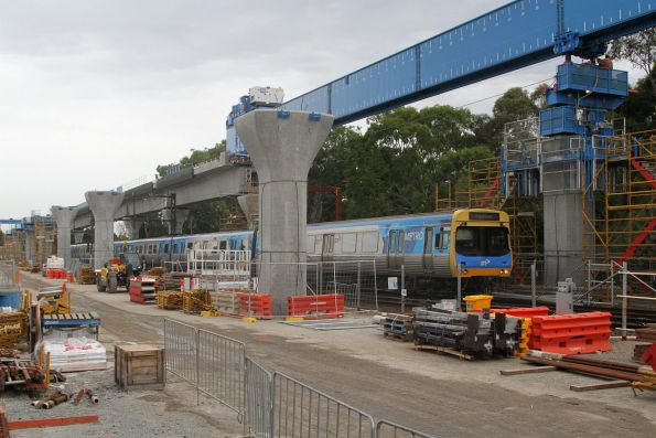 EDI Comeng 366M passes under the incomplete viaduct at Hughesdale on a down Pakenham service