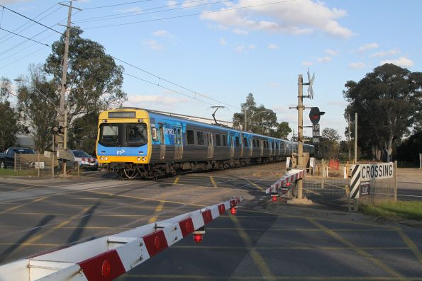 EDI Comeng 516M leads an up Cranbourne service through the Greens Road level crossing in Dandenong South