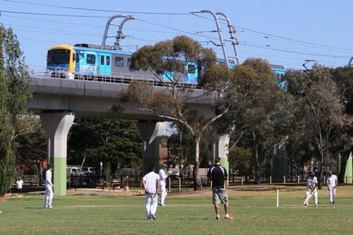 Siemens train passes a cricket game at the Ross Reserve in Noble Park