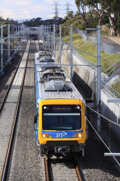With the terminus of South Morang visible in the background, an up train passes under the Pindari Avenue bridge