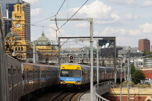 Up service waiting on the Viaduct for a platform at Flinders Street, as a down Comeng vacates one