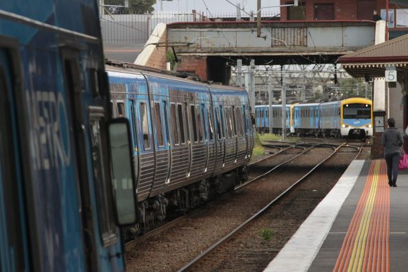 Comeng departs North Melbourne platform 5, as a Siemens train waits for the signal to clear