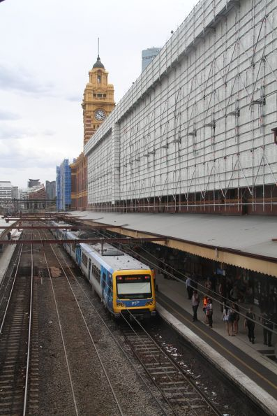 X'Trapolis train departs Flinders Street platform 1, with scaffolding covering the building overhead