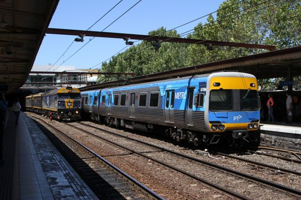 Comeng 679M arrives at Flinders Street platform 10, as the down Maryvale freight runs parallel through track 9A