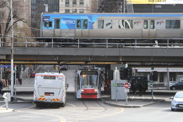 Comeng train 462M passes Transdev Melbourne bus #565 6343AO and tram D1.3538 at Queensbridge and Flinders Street