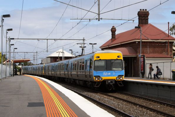 Alstom Comeng 339M passes through Yarraville, with parts of the Metro logo missing