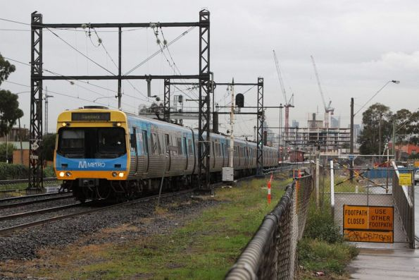 EDI Comeng passes the remains of the Rising Sun footbridge at West Footscray