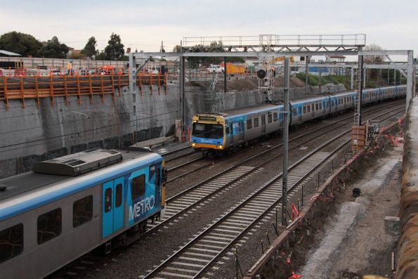 Up Siemens passes a down Comeng in the cutting east of Footscray