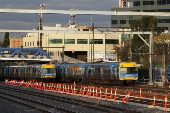 Up and down Comeng trains pass beneath the Albert Street bridge at Footscray