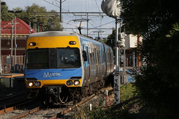 Alstom Comeng train departs Ascot Vale, with a temporary 'Metro' sticker affixed to the front