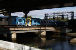 Siemens 836M and 734M pass between Moonee Ponds Creek and the CityLink viaduct with a down Craigieburn service