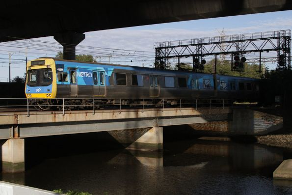 EDI Comeng 485M passes between Moonee Ponds Creek and the CityLink viaduct on an up Craigieburn service