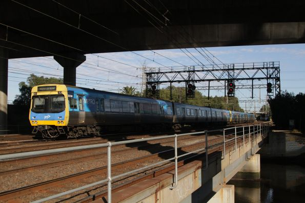 EDI Comeng 351M passes between Moonee Ponds Creek and the CityLink viaduct on a down Watergardens service