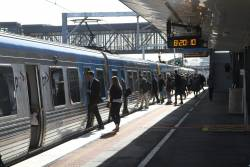 Passengers board a citybound service at West Footscray in morning peak