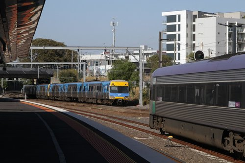 Comeng train on a down Werribee service arrives into Footscray on the suburban lines, with a V/Line train on the parallel RRL tracks
