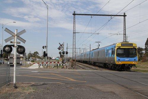 EDI Comeng 473M leads a down Sunbury service across Furlong Road into Ginifer
