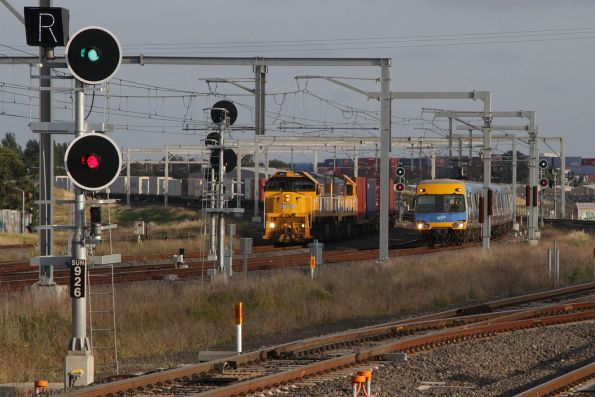 Alstom Comeng arrives into Sunshine on the down, with the down Tocumwal freight in the background