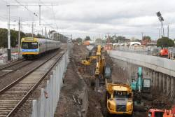 Citybound Comeng train departs St Albans station, as excavators remove rock from the future rail cutting
