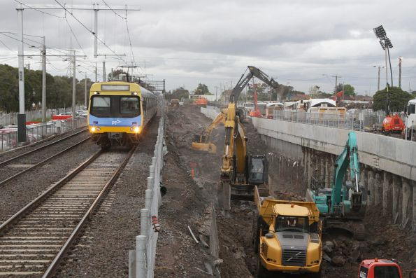 Down Comeng train approaches St Albans station, as excavators remove rock from the future rail cutting