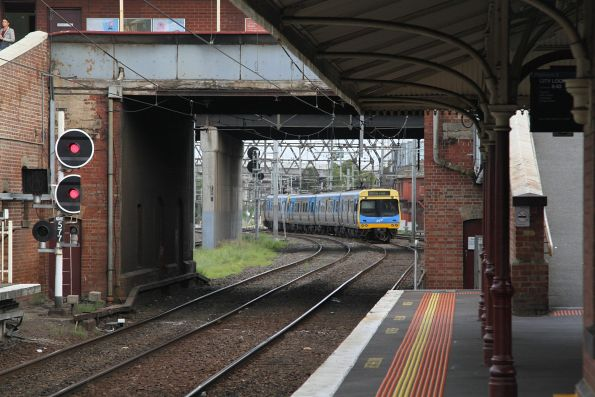 Comeng train ex-Upfield waits outside North Melbourne platform 3, sitting over a crossover and blocking three sets of tracks