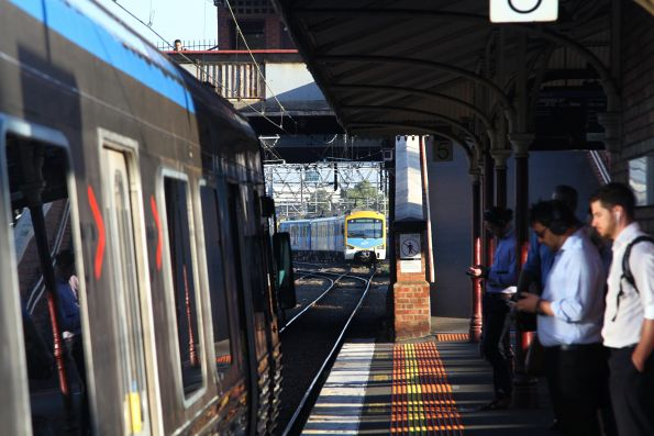 Siemens train waits short of North Melbourne platform 5, as another train clears the platform