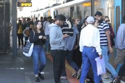 Crowd of passengers at Sunshine boarding a citybound train on a Sunday morning