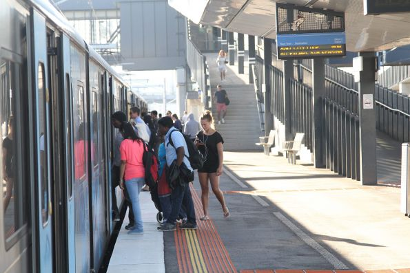 Crowd of passengers at West Footscray boarding a citybound train on a Sunday morning
