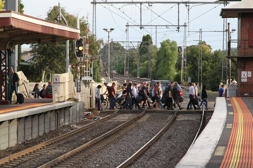 Level crossing clear, as a stream of pedestrians cross the railway at Yarraville