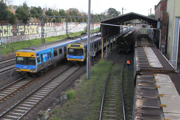 Up and down Craigieburn services pass a grain train at Kensington