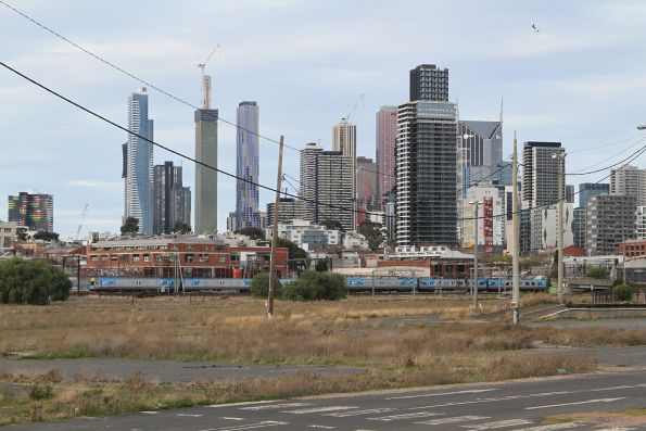 Comeng train passes the Melbourne skyline at North Melbourne