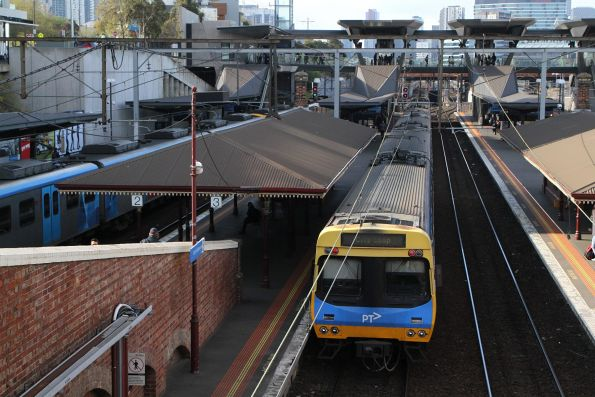 Pair of City Loop bound services at North Melbourne, the train on platform 1 having the signal to proceed