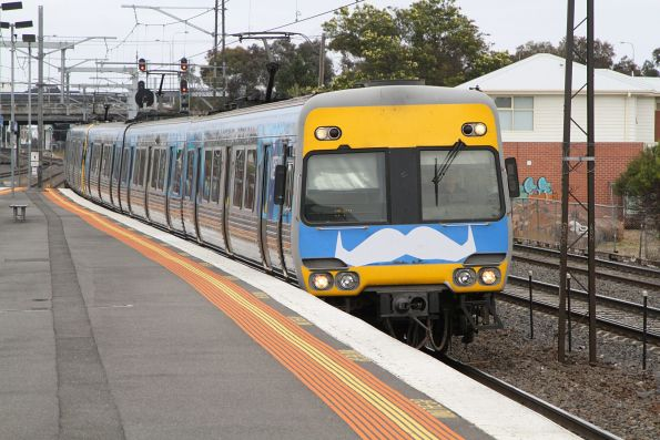 Movember moustache on the front of Alstom Comeng 622M on the up at Middle Footscray