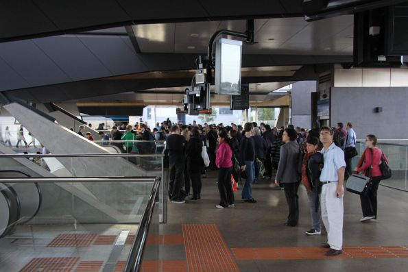 Crowds of passengers waiting on the concourse at North Melbourne station for a train towards the city