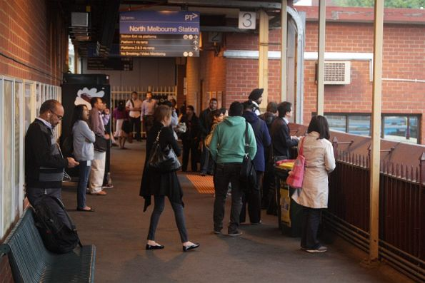 With the platform for the next City Loop train from North Melbourne unknown, passengers wait on the overhead concourse