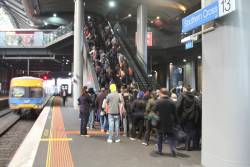 Pack of exiting passengers wait at the bottom of the escalators at Southern Cross platform 13