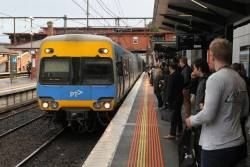Alstom Comeng train arrives into a crowded platform at North Melbourne station