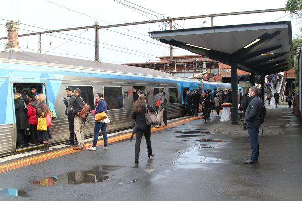 Passengers try to board an already overcrowded City Loop service at North Melbourne station