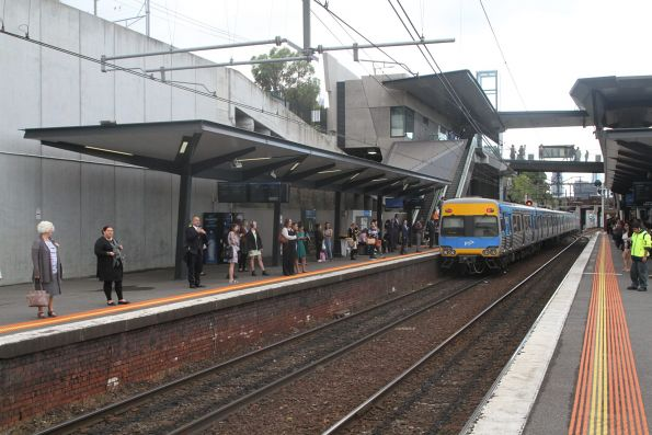 Train heads into the City Loop at North Melbourne platform 1, leaving a crowd of passengers behind