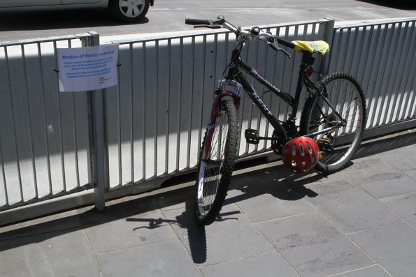 'Notice of fence removal' sign beside bikes chained to the Swanston Street fence beside the Federation Square worksite