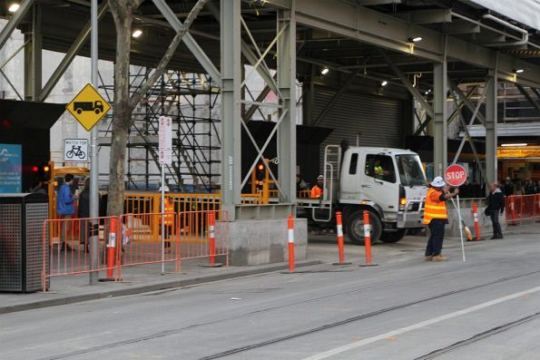 Pedestrian gates closed on Swanston Street as a truck leaves the work site