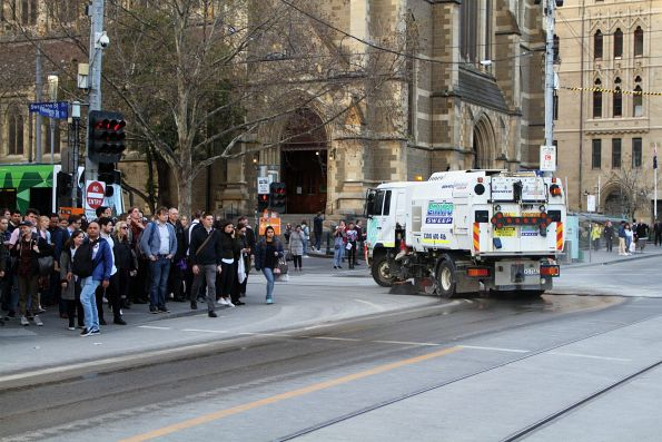 Street sweeper tries to clean up the dust left by trucks at Flinders and Swanston Street