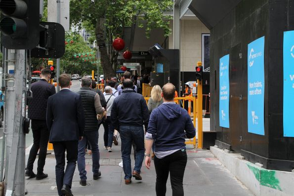 Pedestrians wait for the gates to open at the Metro Tunnel site entrance off Collins Street