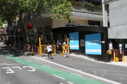 Pedestrian gates close on Collins Street, forcing someone already mid crossing to walk out onto the road