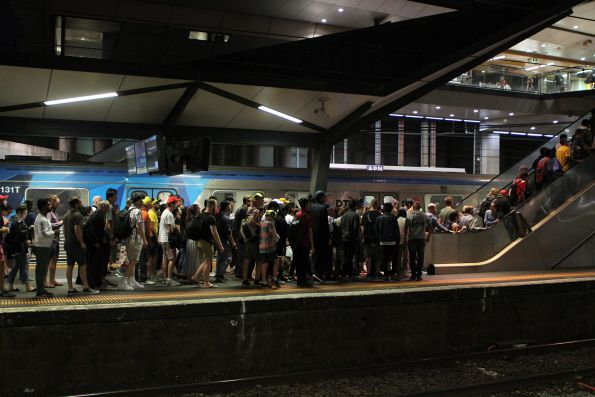 Crowd of Sunbury line passengers change from train to bus at North Melbourne station