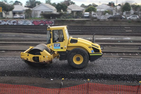 Road roller compacting the ballast  for the replacement down independent goods line