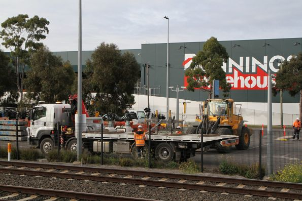 Front end loader unloads a Metro Tunnel branded tilt tray truck at West Footscray